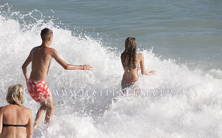 children playing in sea waves